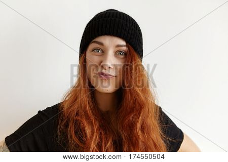Stylish Young European Woman With Messy Hairstyle Wearing Black Hat And T-shirt Pouting Lips, Disple