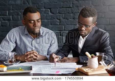 Candid Shot Of African-american Chief Executive Officer In Glasses Pointing Pen At Papers, Showing S