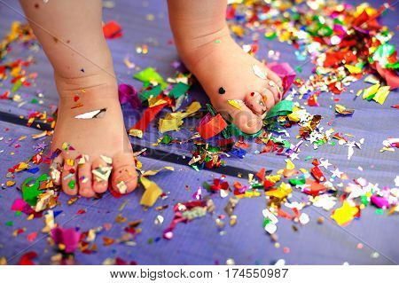 children's birthday party. bare feet are on the floor with confetti