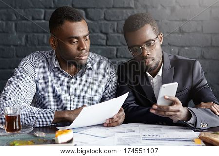 Candida Shot Of Two Confident And Serious African-american Businessmen Focused On Paperwork, Sitting