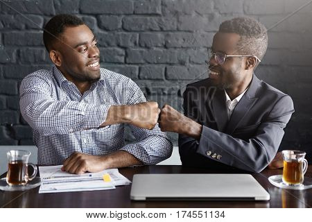 Candid Shot Of Happy Successful Dark-skinned Businessmen Wearing Formal Clothing Fist-bumping While