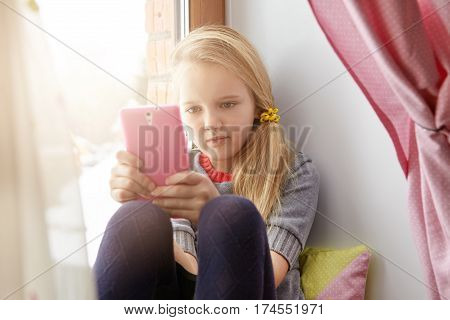 Indoor Shot Of Adorable Little Girl Wearing Her Blonde Hair In Messy Ponytail Relaxing On Windowsill
