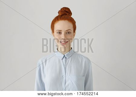 Indoor Shot Of Attractive Young Redhead Female With Hair Bun In Shirt Smiling Happily, Ready For Her