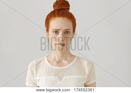 Confused Or Puzzled Beautiful Young Caucasian Woman With Ginger Hair Frowning, Biting Her Lower Lip