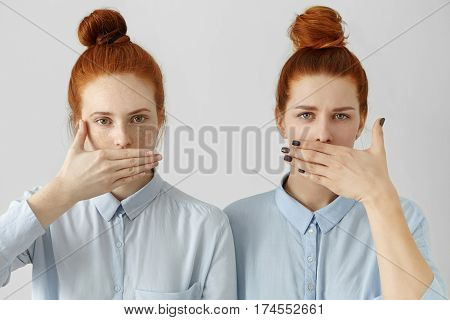 Portrait Of Two Attractive Redhead Women In Identical Shirts Covering Lips With Hands, Having Common