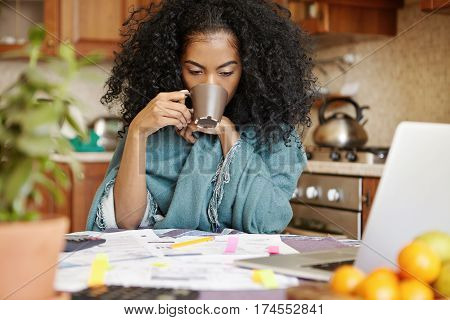 Tired And Unhappy Young African-american Female Drinking Another Cup Of Coffee While Calculating Fin
