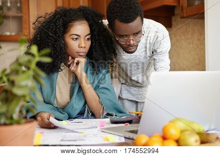 Beautiful Dark-skinned Young Female With Afro Hairstyle Having Worried Look While Managing Family Bu