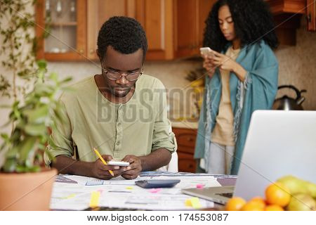 Stressed African Male In Glasses Holding Mobile Phone, Using Online Banking App For Paying Gas And E