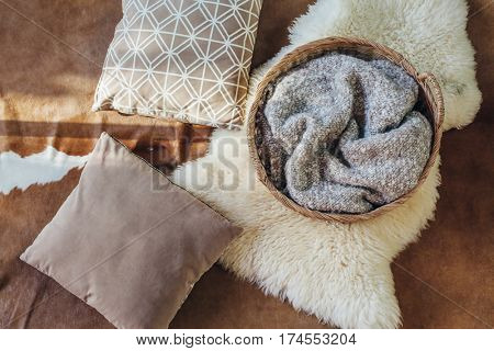 Wicker storage basket with woolen blanket inside and cushions on sheep carpet, top view from above. Natural and organic interior decor.