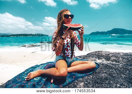 Pre teen girl eating watermelon on the tropical beach in summer sunny day. Holidays on the island and fruit diet.