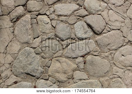 Old Mexican walkway or patio constructed with flat inlaid rocks and cement, uneven surface, crumbling, background.
