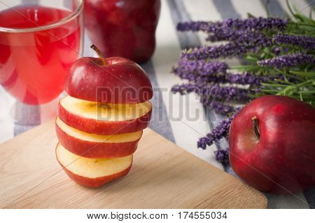 kitchen table with stack of slice apple on cutting board glass of apple juice lavender flower and orange heart shape sign - healthy eating and dieting food concept of health care lifestyle.