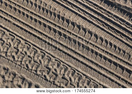 Closeup of tire tread impressions in desert sand, background.