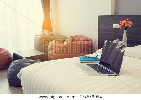 bed with blank screen laptop book modern chair and beautiful flower at bedroom. side view on bed.