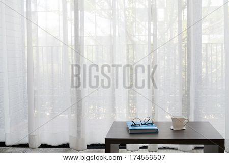 office desk with modern glasses on book white coffee cup on white drape background texture at living room front view on table.