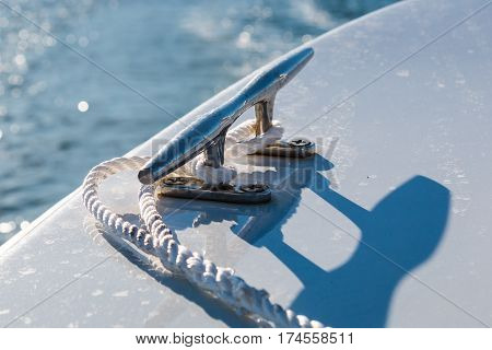Mooring cleat on the stern of a boat with a white rope.