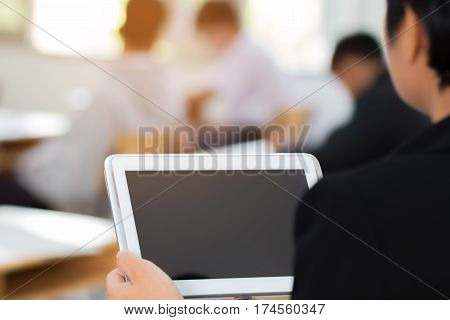 teacher hand holding use tablet with blurred student in classroom background education concept