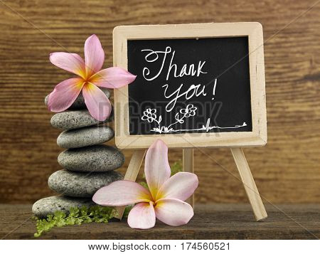 stack of pebbles and mini blackboard with text thank you