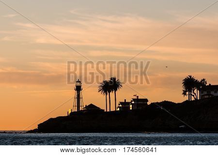 The new Point Loma lighthouse in San Diego, California with surrounding buildings and palm trees against an orange sky.