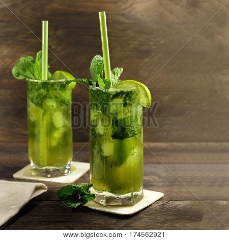 A square photo of mojito cocktails with mint leaves, wedges of lime, and drinking straws, on a dark wooden background with copy space. Selective focus