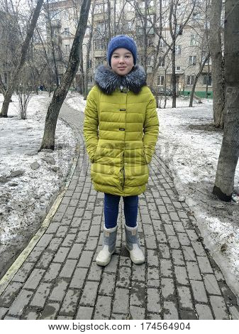 Teen girl in warm clothes in park