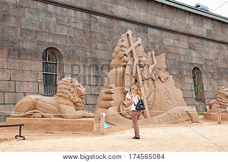 SAINT-PETERSBURG, RUSSIA - AUGUST 15, 2016: Woman takes pictures of the sand sculptures on The Sand Sculpture Festival near The Peter and Paul Fortress Wall
