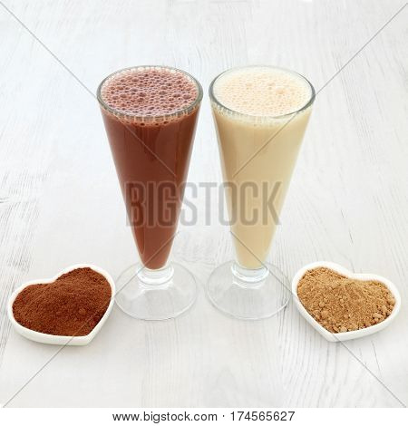 Chocolate whey and maca herb root heath food supplement drinks in glasses with powders. Also used by body builders.