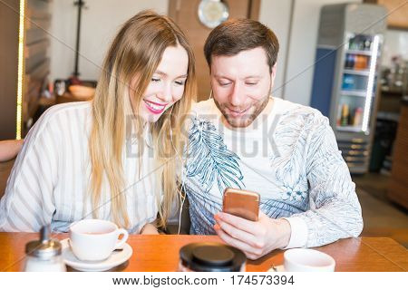 Closeup of couple listening to music with mobile phone at coffee bar. Man and woman listening music with headphones