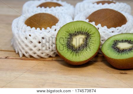 Fresh Kiwi fruit in Foam epe net in paper box, with one cut on half and half.