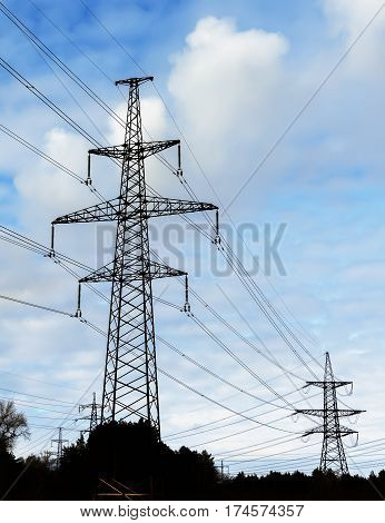 Pylon and transmission power line in sunset.