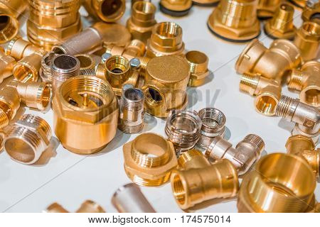 Scattering of various brass sanitary products. Tees, branch pipes, connectors, nipples. Abstract industrial background.