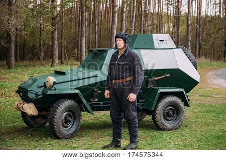 Pribor, Belarus - April 23, 2016: Re-enactor Dressed As Russian Soviet Crew Member Soldier Of World War II Standing At Armoured Soviet Scout Car BA-64 In Forest.