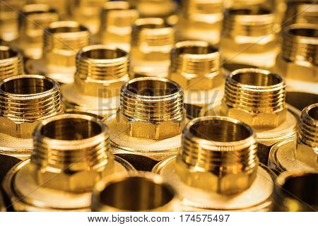 Sanitary Adapter Fittings golden brown. Orderly arranged in neat rows. Abstract industrial background.