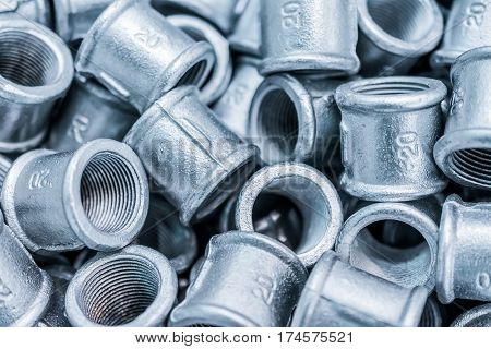 Many of connecting fittings for metal pipes. Small steel castings. Abstract industrial background.