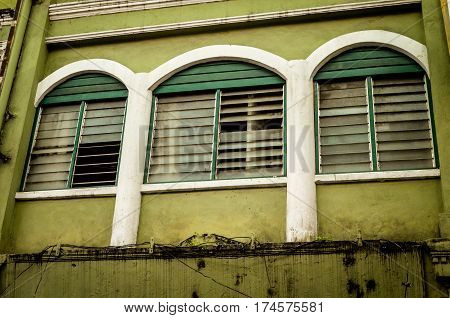 three weathered windows in asian backstreet, malaysia