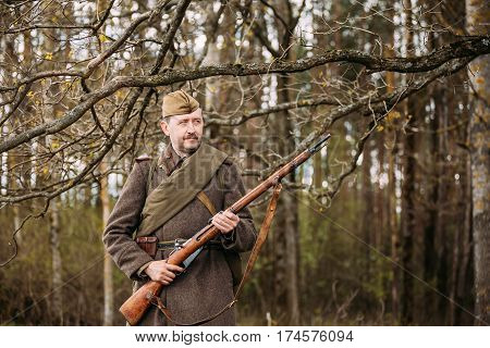 Pribor, Belarus - April 23, 2016: Close up portrait of Re-enactor Dressed As Russian Soviet Infantry Soldier With Rifle Weapon Of World War II In Forest