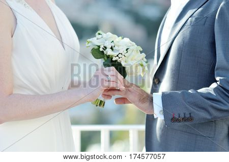 Bride with bouquet putting wedding ring on groom's finger in wedding day