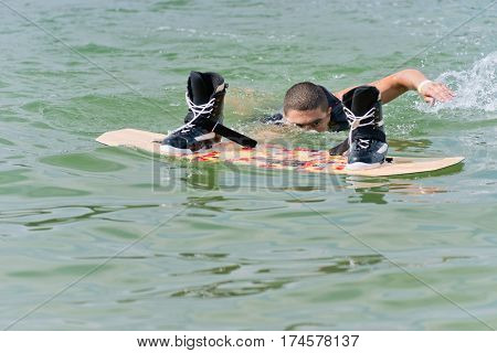Male swimming to wakeboard after fall, toned image