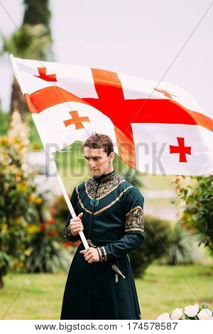 Batumi, Adjara, Georgia - May 26, 2016: Young man in Georgian national dress holding a national flag in celebration of the national holiday - the Independence Day of Georgia.