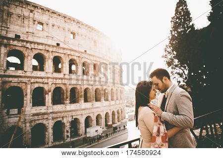 Loving Couple In Front Of The Colosseum In Rome