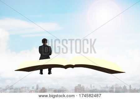 Man Sitting On Book Flying Over City