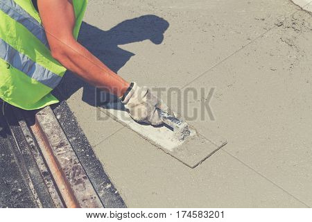 Detail of a construction worker leveling concrete pavement.