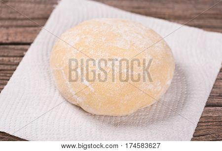 Soft dough on the kitchen napkin over wooden surface background