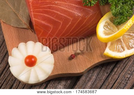 Smoked salmon fillet with vegetables on the cutting board on the old wooden surface