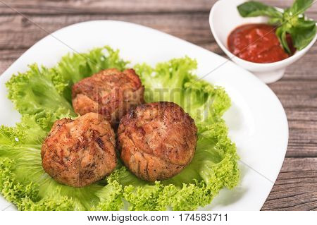 Tasty baked cutlets with green lettuce leaves over old wooden background