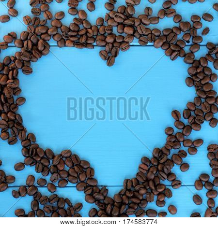 flat layout of the roasted beans forming a heart shape on blue wooden surface / favorite brand coffee