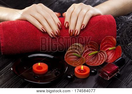 beautiful red manicure with oil and candles, red calla flower and towel on the black wooden table.