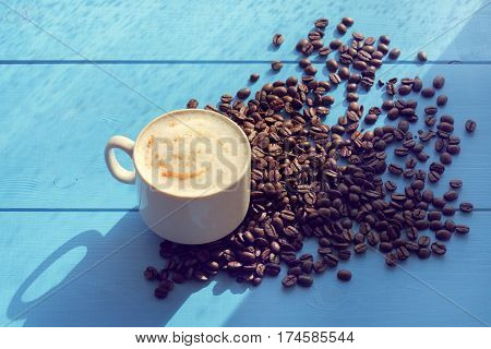 cup of frothy cappuccino flavored with cinnamon standing on a blue table in a pile of coffee beans / spring sunny coffee