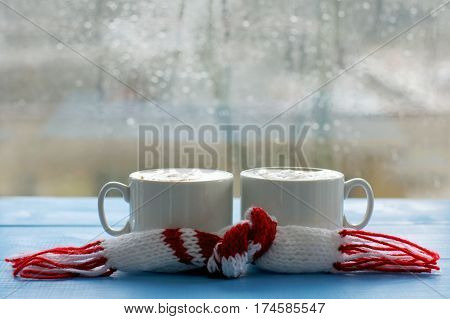 two cups of frothy cappuccino with a scarf on the background of the window with drops after the rain / warming atmosphere of spring coffee break