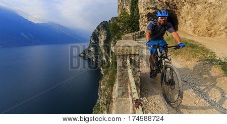 Mountain biking man at sunris eover Lake Garda on path Sentiero della Ponale, Riva del Garda, Italy